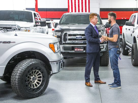 Shane Beus, left, owner of B5 Motors in Gilbert, presents
