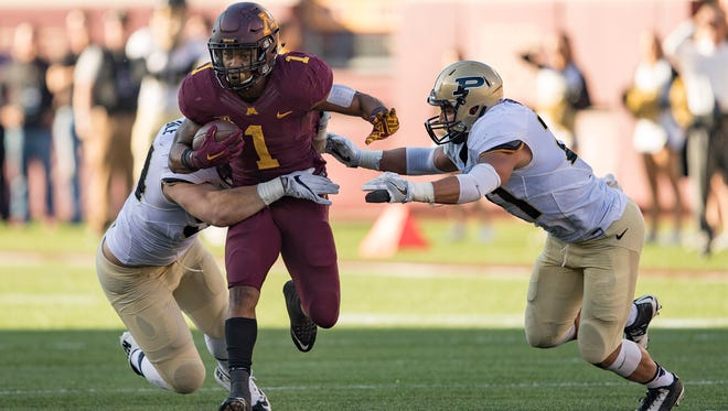 Minnesota running back Rodney Smith (1) rushes with the ball and breaks a tackle from Purdue Boilermakers linebacker Markus Bailey (21) and defensive tackle Jake Replogle (54) in the first half at TCF Bank Stadium.