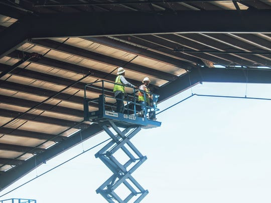 National Construction crew workers work on the awning that was constructed at the Otero County Fair and Rodeo Fairgrounds Friday morning.