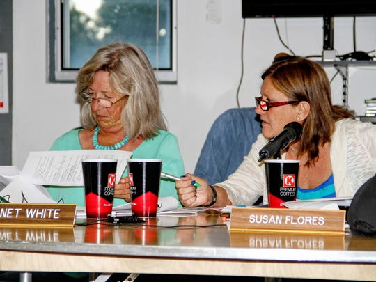 In this file photo, County Commissioners Janet White and Susan Flores review a volunteer firefighters/EMS standards policy at a public hearing in the Village of Cloudcroft earlier in June.