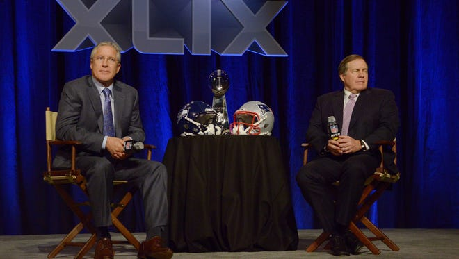 Seattle Seahawks head coach Pete Carroll (left) and New England Patriots head coach Bill Belichick (right) during a joint press conference for Super Bowl XLIX at Phoenix Convention Center.