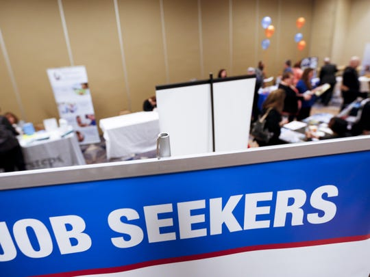 In this file photo, display signs designed to attract employment seekers line the booths of job recruiters at a Job Fair in Pittsburgh. (AP Photo/Keith Srakocic)
