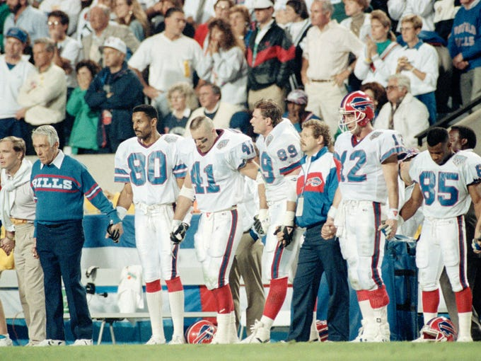 Members of the Buffalo Bills hold hands on the sidelines as they watch Scott Norwood attempt a field goal that could've won the Bills Super Bowl XXV.