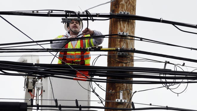 A utility worker attaches wires on a power pole.