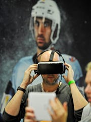 James Lunn of Savvy Marketing, tests out a virtual reality presentation that puts fans on the ice with the player in a virtual experience at the NHL Fan Fair inside Music City Center Wednesday Jan. 27, 2016, in Nashville, Tenn.