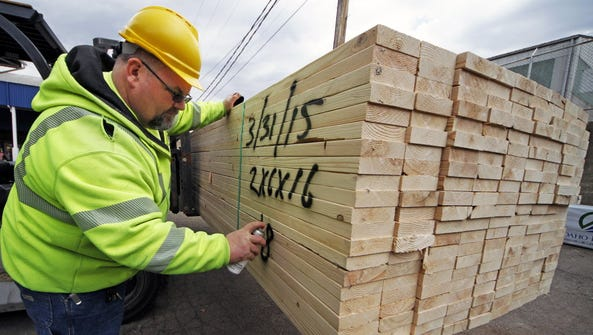Roy Livesey marks a pallet of 2x4's at the Allegheny
