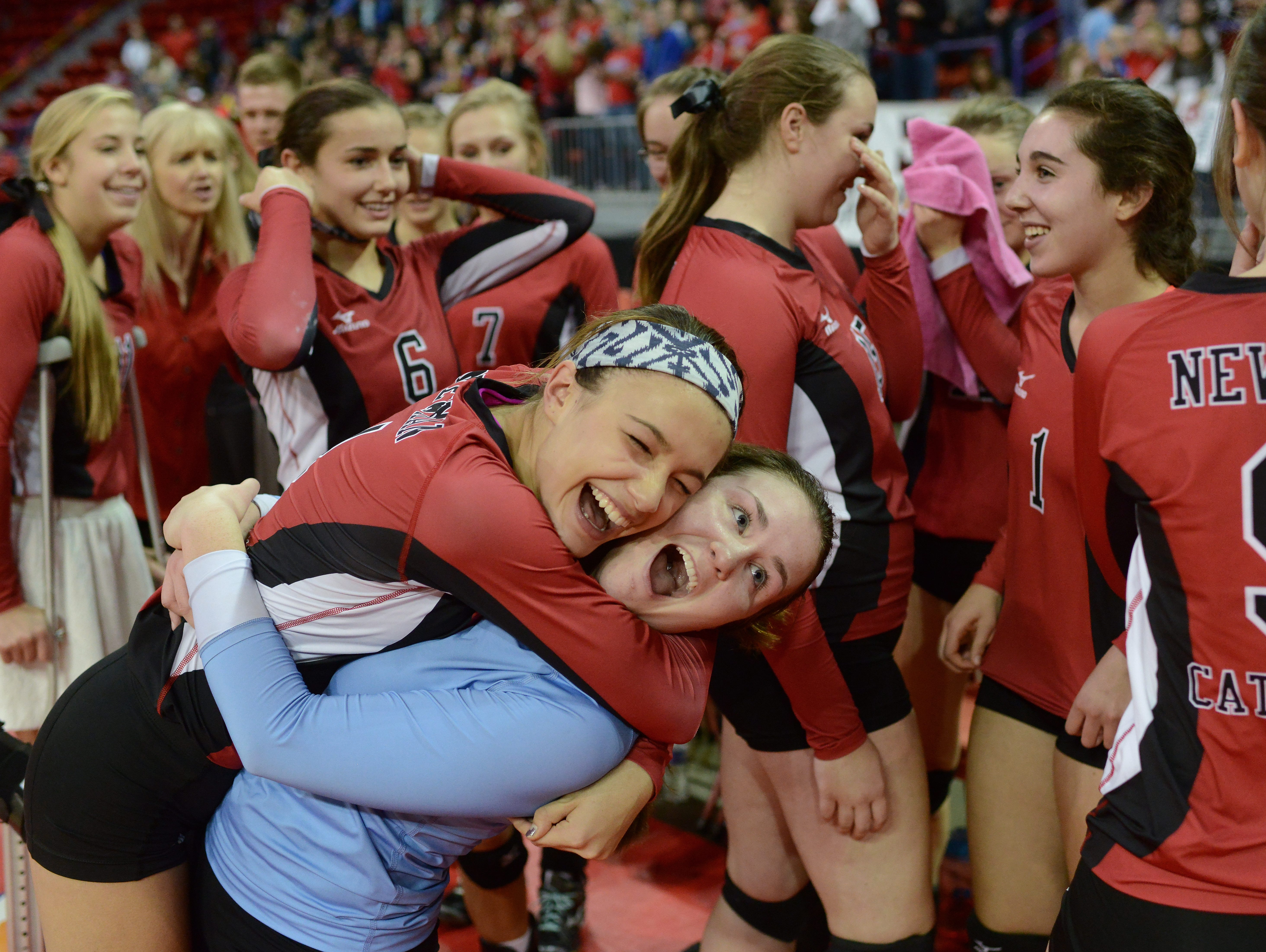 Newman Catholic setter Rylie Vaughn leaps on libero Breck Wcisel as they celebrate their victory in the WIAA Division 4 State Championship volleyball match at the Resch Center in Ashwaubenon Saturday. Newman Catholic defeated Southwestern in four sets.