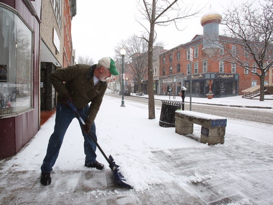 Charlie Kavana shovels the snow outside the Robert