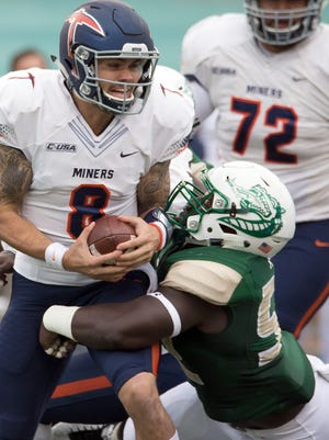 UTEP Miners quarterback Zack Greenlee gets sacked by UAB Blazers linebacker Fitzgerald Mofor during first quarter at Legion Field.