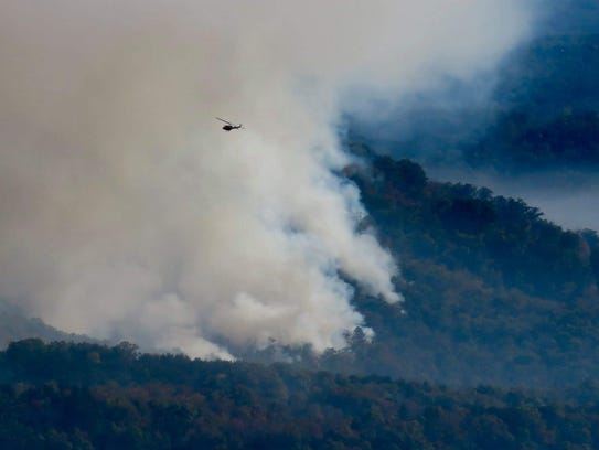 A helicopter drops water on the Party Rock Fire near