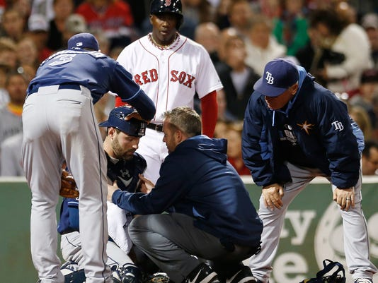 Tampa Bay Rays' Evan Longoria (3) and a trainer check on Curt Casali as Rays manager Joe Maddon, right, watches after Casali was hit by a foul tip from Boston Red Sox's Rusney Castillo, rear, during the fourth inning of a baseball game in Boston, Wednesday, Sept. 24, 2014. (AP Photo/Michael Dwyer)