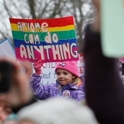 A young girl holds up signage Sunday, Jan. 21, 2018,
