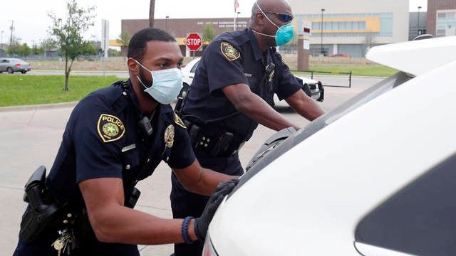 In this April 9 photo, amid concerns of the spread of COVID-19, Dallas ISD police officers Mylon Taylor, left, and Gary Pierre push a car that ran out of gas while waiting in line for the weekly school meal pick up for students in Dallas. The coronavirus pandemic that has crippled big-box retailers and mom and pop shops worldwide may be making a dent in illicit business, too.