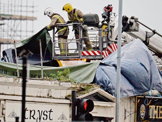 Rescue workers investigate the scene at a pub on Stockwell Street where a police helicopter crashed on the banks of the River Clyde in Glasgow, Scotland, in the United Kingdom. Scotland Police have confirmed eight deaths.