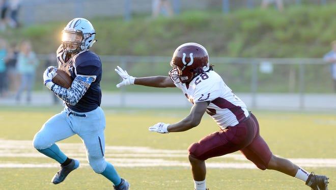 Enka's Michael Cantrell runs the ball past Owen's Sidney Gibbs during their game at Enka High School last week.