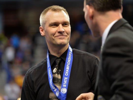 Tech head coach Joel Stark-Haws accepts his first place medal in the Class 2A state high school state gymnastics team championship meet in 2016.