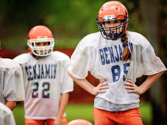Offense and defense tackle Madeline Hart (right) awaits another drill from coach Greg Keller. Hart, and Emma Shirzad (left), are two Jupiter-area girls who have spent this season on the gridiron, holding their own among on an eighth-grade football team full of male players.