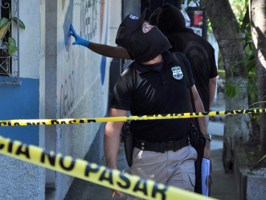 Forensic personnel work on the crime scene where a
