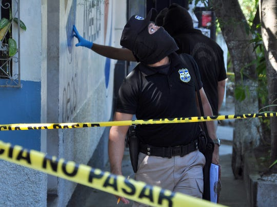 Forensic personnel work on the crime scene where a woman was murdered by presumed gang members in San Salvador on Jan. 3, 2016. Officials in El Salvador, one of the world's most dangerous places, last week said that for the first time in nearly two years, the country passed an entire day without a homicide.