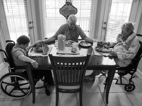 """Surrounded by his """"girls,"""" Fred Shultz says grace before a dinner of Salisbury steak, macaroni and cheese and bean salad. Tanya Shultz, 45, left, lives with her parents and, like her mom, Patty, also uses a wheelchair to get around the home. Fred has given up just about all of the cooking duties choosing instead to visit the local Schnucks deli for evening meals he can easily warm and serve."""