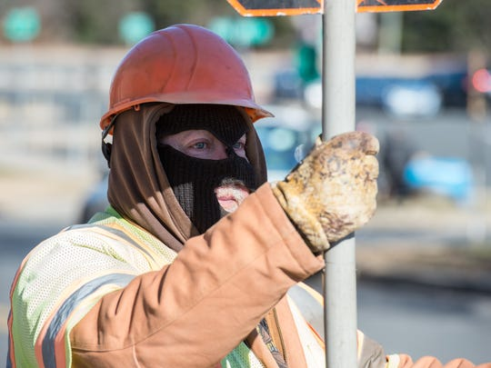 A construction worker stands in the cold wearing a balaclava in 23 degree weather at the intersection of West Main Street and Poplar Hill Avenue on Thursday, Dec. 28, 2017.