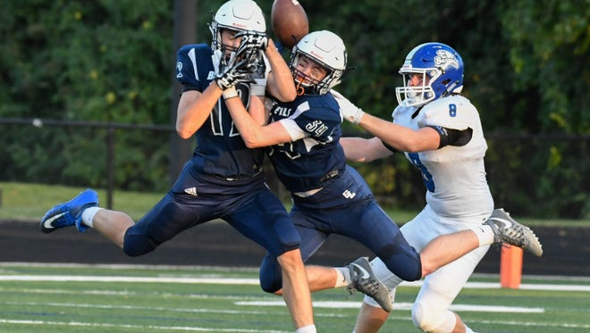 Two Gull Lake defenders collide while going for a Harper Creek pass late in the second quarter of play in action earlier this year