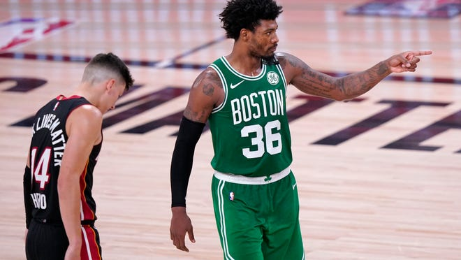 Miami Heat's Tyler Herro (14) stands by as Boston Celtics' Marcus Smart (36) gestures on the court after sinking a basket during the second half of an NBA conference final playoff basketball game, Saturday, Sept. 19, 2020, in Lake Buena Vista, Fla.