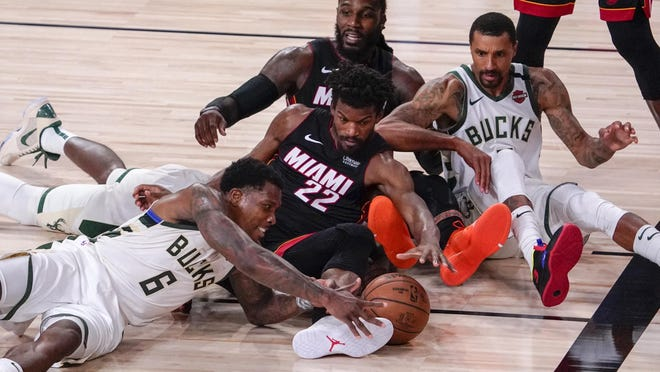 Milwaukee Bucks' Eric Bledsoe and Miami Heat's Jimmy Butler go after a loose ball during the second half of an NBA conference semifinal playoff basketball game Sunday, Sept. 6, 2020, in Lake Buena Vista, Fla.