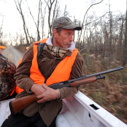 Dale Robison looks into the woods as hunters ride to