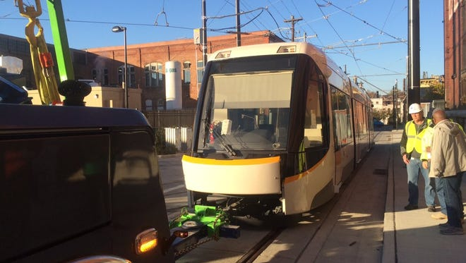 Workers prepare the streetcar for its first trip through town via dead pull.