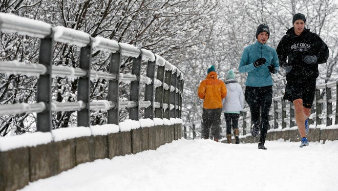 People jog on a footbridge to the Esplanade in Boston on Jan. 24, 2015.