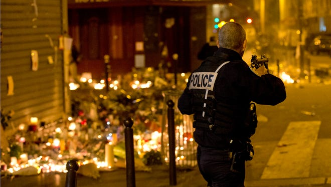 A French police officer stands near tributes to the victims of the Paris attacks.