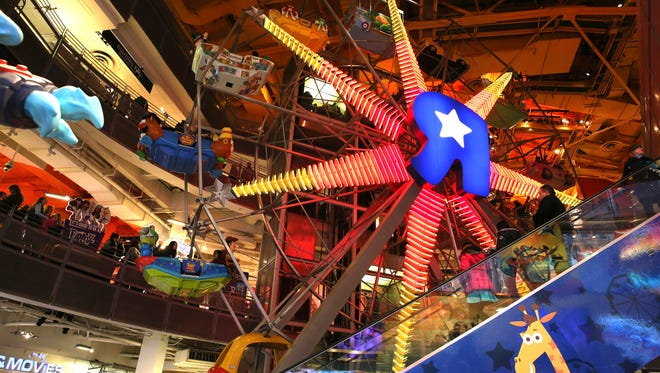 The Ferris Wheel at the Toys R Us store in New York's Times Square is seen, Wednesday, Dec. 30, 2015. Fourteen years after it began wowing millions of tourists with its indoor 60-foot Ferris wheel and a growling 20-foot Tyrannosaurus, the giant Toys R Us flagship store in Times Square closes its doors Wednesday. (AP Photo/Mary Altaffer) ORG XMIT: NYMA112