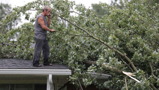 Harold Staten talks on a cellphone while surveying damage to his roof after a tornado touched down in Brownsburg's Rolling Acres Neighborhood on Monday Aug. 15, 2016.