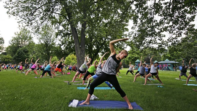 Jamie Schumacher of Appleton takes part in Empower Yoga in City Park Wednesday in Appleton. The free event goes on each Wednesday during the summer.