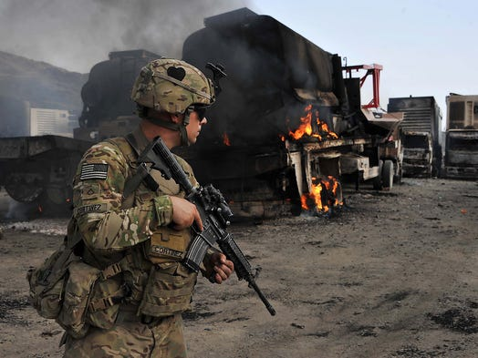 A U.S. soldier investigates the scene of a suicide bombing at the border crossing between Afghanistan and Pakistan on June 19 in Torkham, Nangarhar province, Afghanistan. Three Taliban suicide bombers attacked and burned 37 NATO military fuel vehicles during an assault on an outpost along the main supply route for coalition forces.