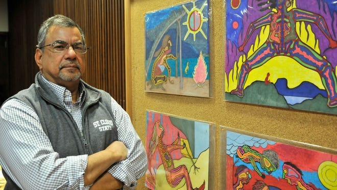 Jim Knutson-Kolodzne, director of the American Indian Center at St. Cloud State University, showed off some of the art up for bid in a silent auction Monday in the theater at Atwood Memorial Center. These pieces are by area artist William Wilson. Proceeds from the auction help offset the cost of this weekend's powwow, which Knutson-Kolodzne said would attract about 1,000 people and cost about $16,000. Costs include paying a professional staff of about 10, among them an emcee, honor guard, head male and female dancers and a spiritual leader.