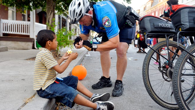 York City Police lieutenant Erik Kleynen, right, attaches a pin to a toy deputy badge given to him by Juan Andrew Martinez, 6, during National Night Out on Tuesday, Aug. 4, 2015, in the 200 block of East College Street in York City. Various municipalities and police departments in York County teamed up to host National Night Out, an annual, nationwide event designed to strengthen relationships between communities and police. York City, the York City Police Department and other community and religious groups hosted 27 National Night Out block parties throughout the city.