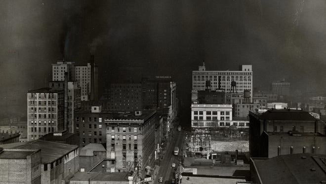 Thick winter smoke accumulated over downtown Louisville business district in 1943 as the camera lens looks north on 4th Street.  Photo by Al Blunk, THE COURIER-JOURNAL Nov 28 1943