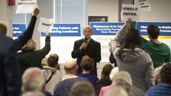 U.S. Rep. Tim Walberg, R-Mich., speaks as people stand