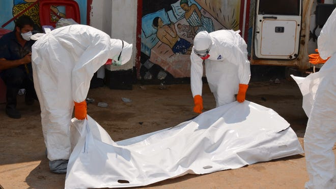 Liberian Red Cross health workers wearing protective suits carry the body of victim of the Ebola virus on September 12, 2014 in a district of Monrovia. Liberia has been hit hard by the Ebola epidemic, the worst in history, which has killed more than 2,400 people since it erupted earlier this year, according to World Health Organization. AFP PHOTO / ZOOM DOSSOZOOM DOSSO/AFP/Getty Images