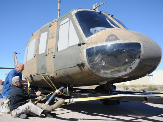 Jim Harbison, foreground, and Jay Lloyd strap a Huey