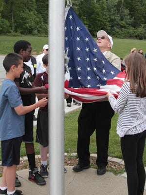 Veteran Jay Vreeland, of Post 1776 of Washington Township, helps the students raise the flag in observance of Memorial Day at Benedict A. Cucinella Elementary School.