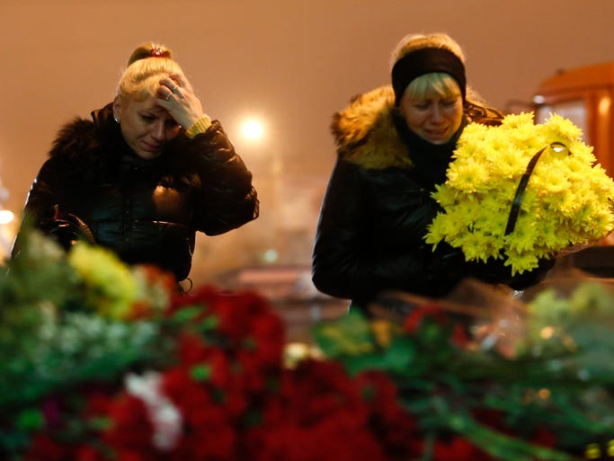 Women lay flowers outside the Volgograd main railway station in Volgograd, Russia, early Dec. 30, a day after a suicide bombing there. Russian authorities ordered police to beef up security at train stations and other facilities across the country after another suicide bombing Dec. 30.