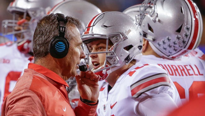 Ohio State head coach Urban Meyer talks to on his headset as quarterback Joe Burrow (10) talks to a different person, during a time out in the second half of an NCAA college football game against Nebraska in Lincoln, Neb., Saturday, Oct. 14, 2017. Ohio State won 56-14. (AP Photo/Nati Harnik)