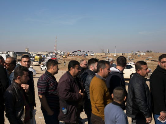 Men wait in line for permission to cross the Khazer