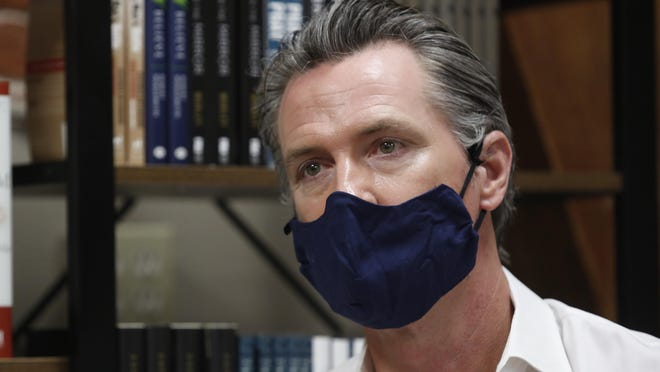 Gov. Gavin Newsom wears a face mask during his stop at the Legendary Coffee and Books in Stockton on June 4. Newsom's administration on Thursday mandated that Californians wear masks in most indoor settings as the state continues to battle the coronavirus.