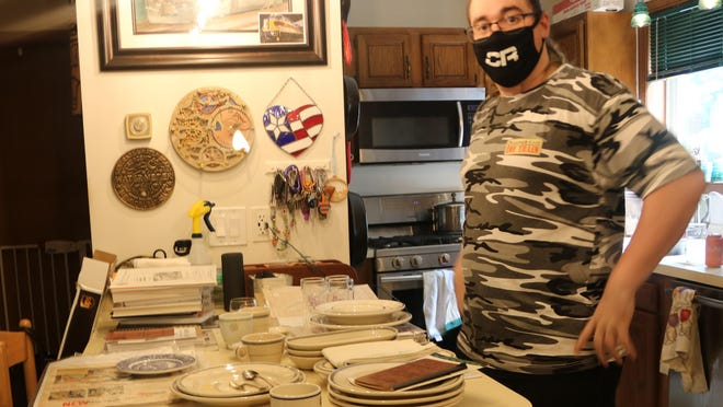Rudy Garbely, president of the Conrail Historical Society, wears his Conrail mask and displays his collection of Atlantic Coastline dining car dishes. His book on Conrail cabooses was just published.