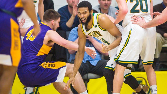 The University of Vermont's Dre Wills controls the ball against the University of Albany's Greig Stire in Burlington on Wednesday, February 22, 2017.