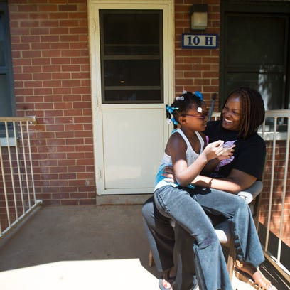 Pamela Smith sits on her front porch with Promise Wyatt,